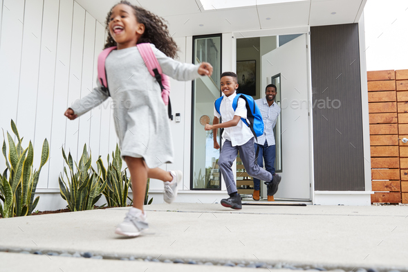 Excited Children Running Out Of Front Door On Way To School Watched By Father - Stock Photo - Images