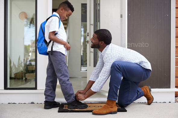 Father Tying Sons Shoelaces As He Leaves For School - Stock Photo - Images