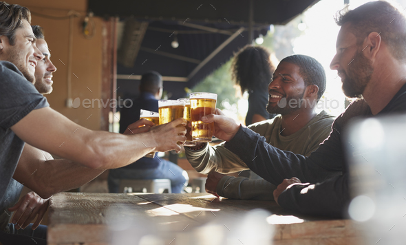 Group Of Male Friends Meeting In Sports Bar Making Toast Together - Stock Photo - Images