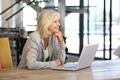 smiling older woman working laptop computer indoors - PhotoDune Item for Sale