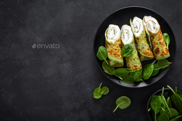Savory crepes with spinach and feta cheese on black background, top view - Stock Photo - Images
