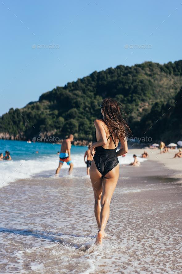 Brunette woman swimsuit and sunglasses runs along seashore - Stock Photo - Images