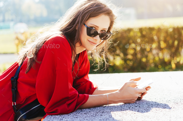 Portrait photo of a young girl with a smartphone - Stock Photo - Images