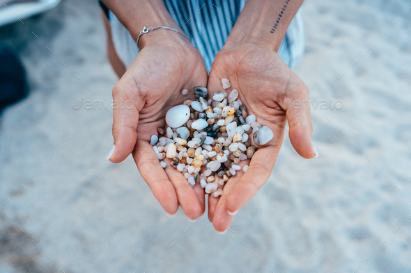 Women's hands are holding a lot of small pebbles - Stock Photo - Images