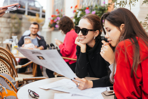 Two beautiful stylish women sitting at the table in street cafe - Stock Photo - Images