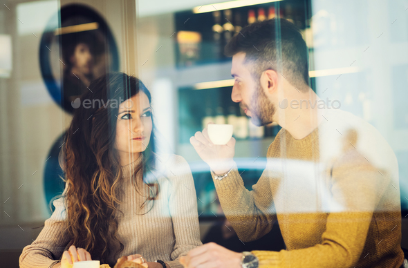 Couple drinking an espresso. Reflected between the window. - Stock Photo - Images