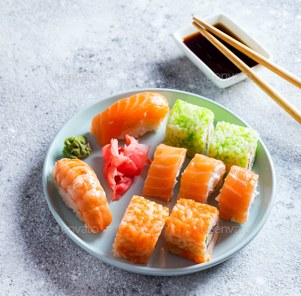 Various sushi on ceramic plate with metal Korean sticks on light stone background with green leaves - Stock Photo - Images
