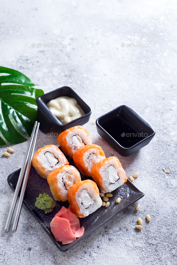 cream cheese Philadelphia roll classic on a stone black plate with chopsticks and sauce . Japanese - Stock Photo - Images