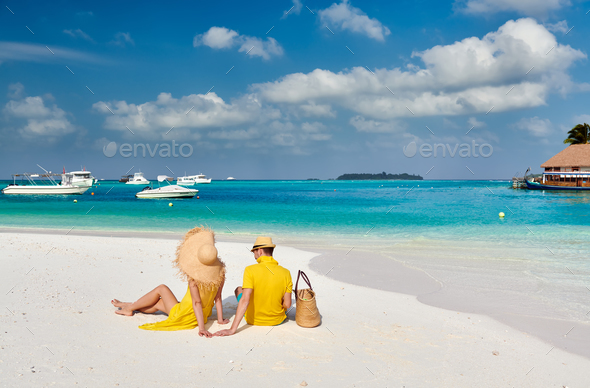 Couple in yellow on tropical beach at Maldives - Stock Photo - Images
