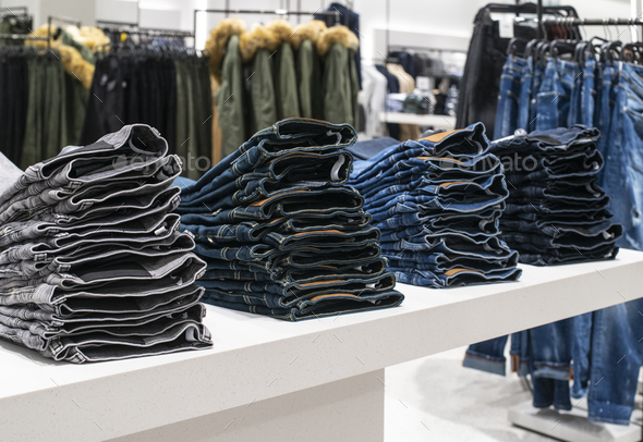 Blouses and jeans on shelf in fashion clothing store. Casual clo - Stock Photo - Images