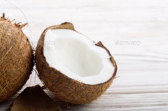 Coconut and shell pieces on white wooden table - Stock Photo - Images