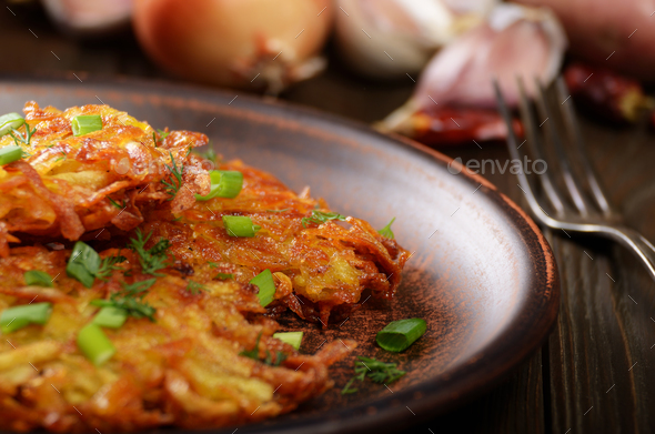 Fresh homemade tasty potato pancakes in clay dish with vegetable - Stock Photo - Images