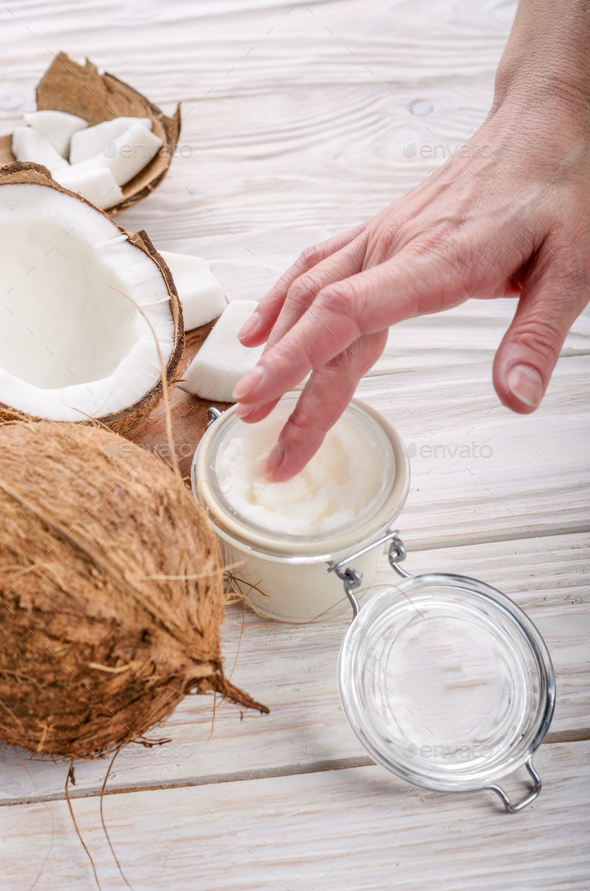Coconut oil on human palm and in airtight glass jar with shell p - Stock Photo - Images