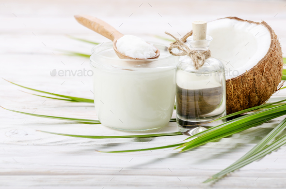 Coconut shell liquid and hard oil in glass jar on white wooden t - Stock Photo - Images