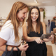 Two Female Friends Looking At Mobile Phone As They Shop In Independent Fashion Store - PhotoDune Item for Sale