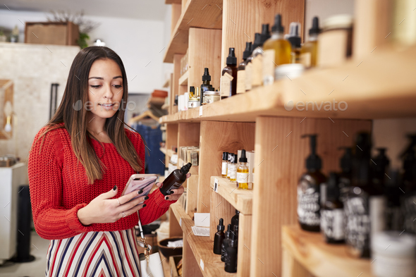 Female Customer Shopping In Independent Cosmetics Store Comparing Prices Using Mobile Phone - Stock Photo - Images