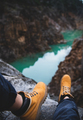 Feet of nature explorer sitting over mountain river canyon - PhotoDune Item for Sale