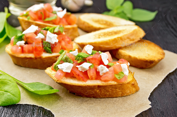 Bruschetta with tomato and cheese on dark board - Stock Photo - Images