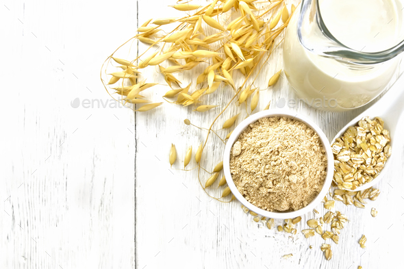 Flour oat in bowl with milk on board top - Stock Photo - Images