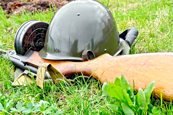 Helmet and submachine gun on grass - Stock Photo - Images