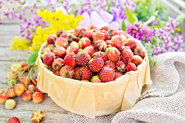 Strawberries in box with flowers on board - Stock Photo - Images