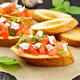 Bruschetta with tomato and cheese on dark board - PhotoDune Item for Sale
