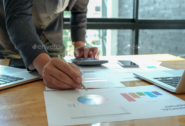 Hand businessman work on calculator and write graphs in office. - Stock Photo - Images