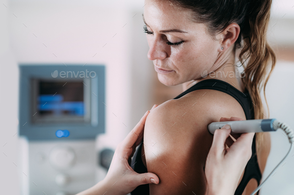 Laser therapy. Physical therapist treating patient's shoulder - Stock Photo - Images