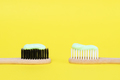 Bamboo toothbrushes with organic toothpaste on yellow background - PhotoDune Item for Sale