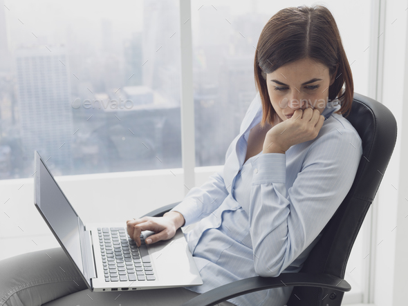 Pensive businesswoman working with her laptop - Stock Photo - Images