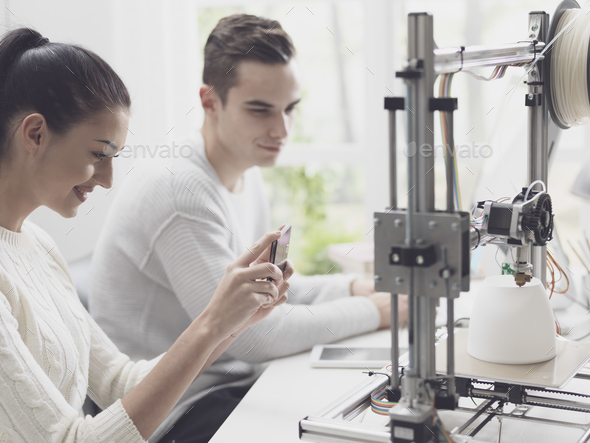 Academic students using a 3D printer in the lab - Stock Photo - Images