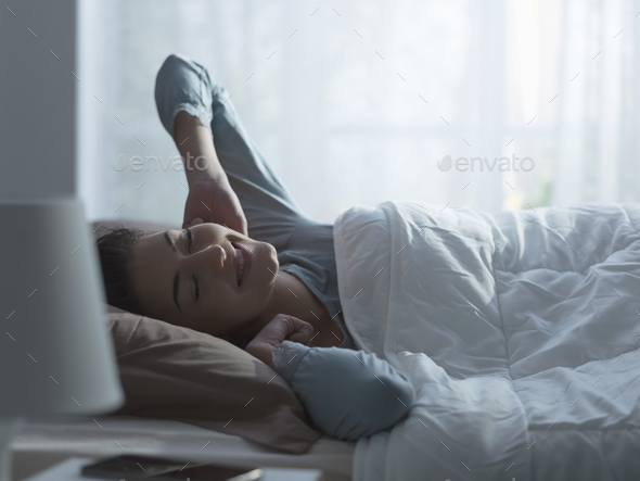 Happy relaxed woman waking up early in the morning - Stock Photo - Images