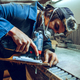 Carpenter using circular saw for cutting wooden boards. - PhotoDune Item for Sale