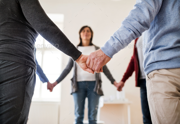 Midsection of people standing in a circle and holding hands during group therapy. - Stock Photo - Images