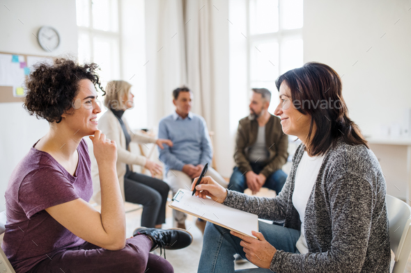 Senior counsellor with clipboard talking to a woman during group therapy. - Stock Photo - Images