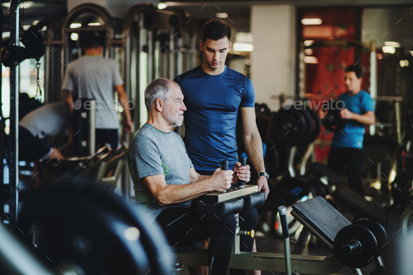 A senior man with a young trainer doing strength workout exercise in gym. - Stock Photo - Images