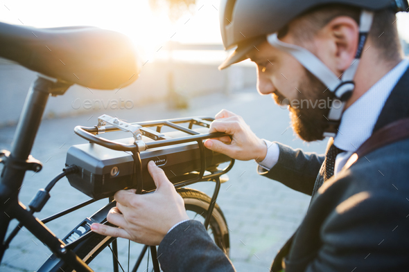 Hipster businessman commuter setting up electric bicycle in city. - Stock Photo - Images