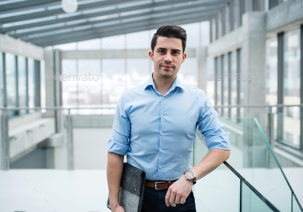 A young businessman standing in corridor outside office. - Stock Photo - Images