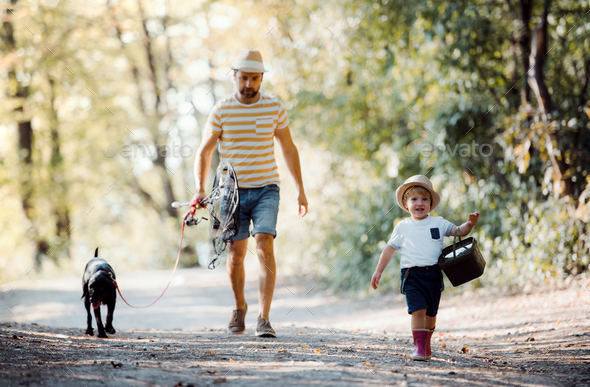A mature father with a small toddler son and a dog going fishing. - Stock Photo - Images