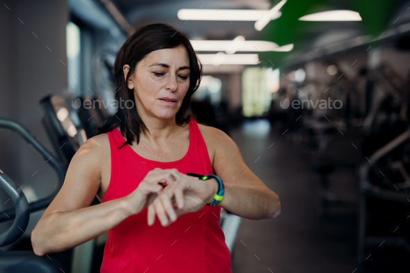 A senior woman in gym resting after doing exercise, checking time. - Stock Photo - Images