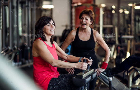 Two cheerful senior women in gym doing strength workout exercise. - Stock Photo - Images