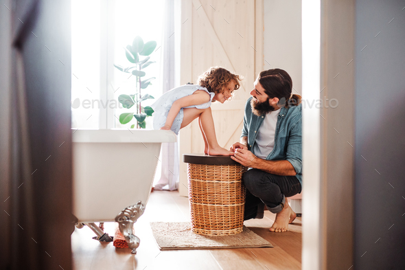 Young father painting small daugter's nails in a bathroom at home. - Stock Photo - Images