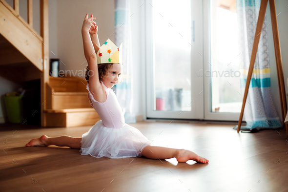 A small girl with a princess crown at home, doing gymnastic split. - Stock Photo - Images