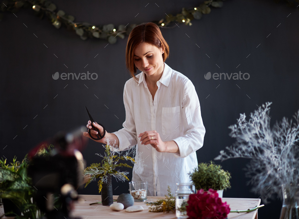 Young creative woman vlogger in a flower shop. A startup of florist business. - Stock Photo - Images