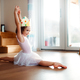 A small girl with a princess crown at home, doing gymnastic split. - PhotoDune Item for Sale