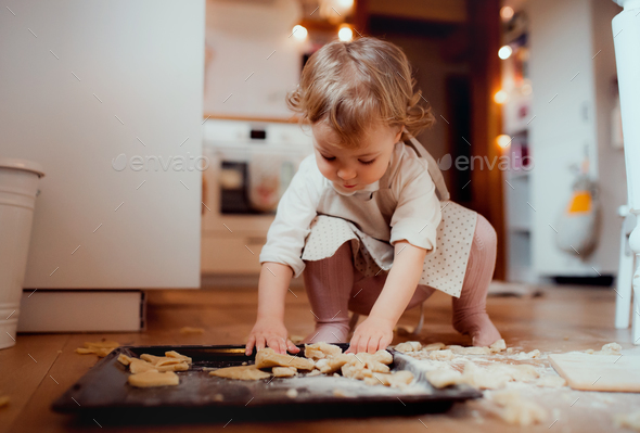 A small toddler girl making cakes on the floor in the kitchen at home. - Stock Photo - Images
