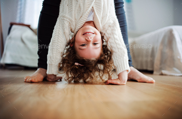 An unrecognizable mother holding small girl upside down at home. - Stock Photo - Images