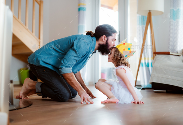 A side view of small girl with a princess crown and young father at home, playing. - Stock Photo - Images