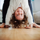 An unrecognizable mother holding small girl upside down at home. - PhotoDune Item for Sale