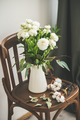 Spring white buttercup flowers in enamel jug on wooden chair - PhotoDune Item for Sale